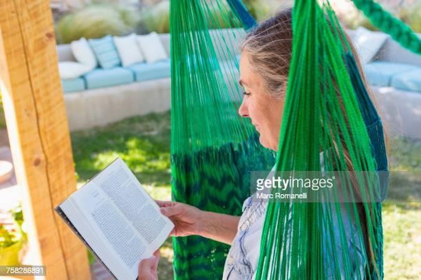 Older Caucasian woman reading book in green hammock