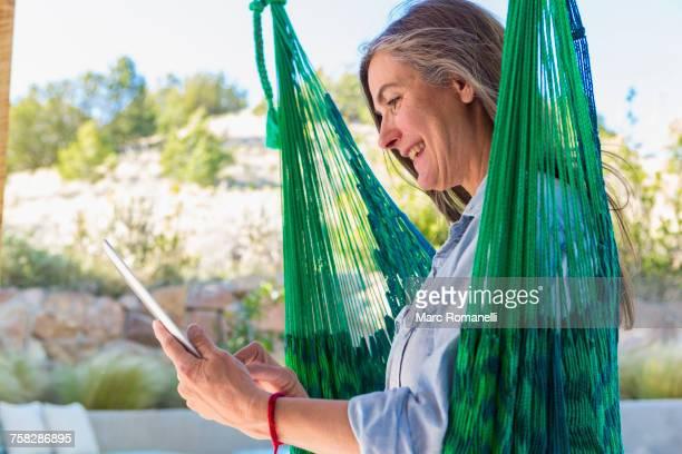 Older Caucasian woman reading digital tablet in green hammock