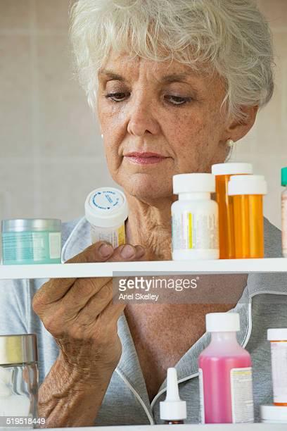 Older Caucasian woman reading prescription medicine