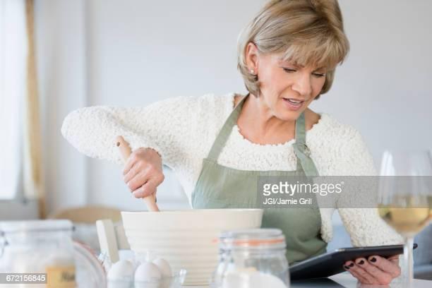 Older Caucasian woman reading recipe on digital tablet