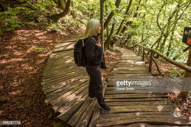 Older Caucasian woman reading sign on wooden pathway in forest