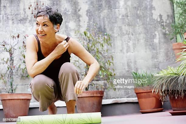 Older Caucasian woman rolling up yoga mat in courtyard