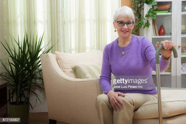 Older Caucasian woman sitting and holding cane