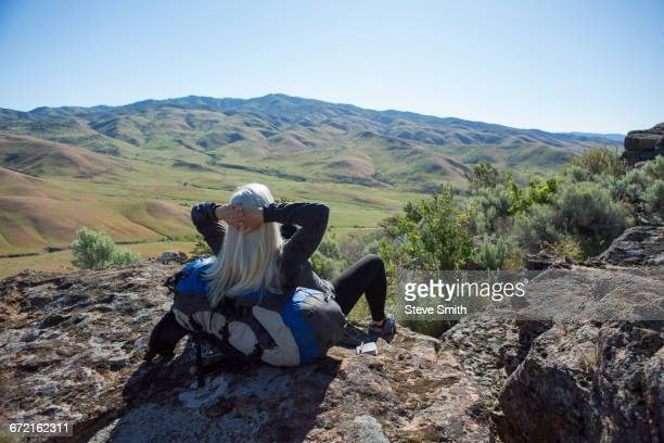 older caucasian woman sitting on rocks leaning on backpack - boise idaho stock pictures, royalty-free photos & images