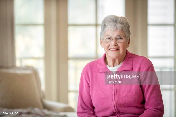 Older Caucasian woman smiling in bedroom