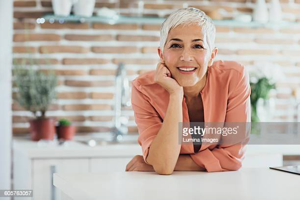 older caucasian woman smiling in kitchen - kin in de hand stockfoto's en -beelden