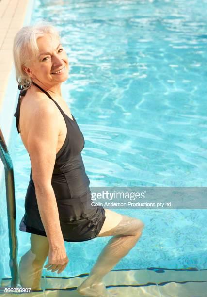 Older Caucasian woman smiling in swimming pool