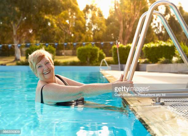 Older Caucasian woman smiling in swimming pool