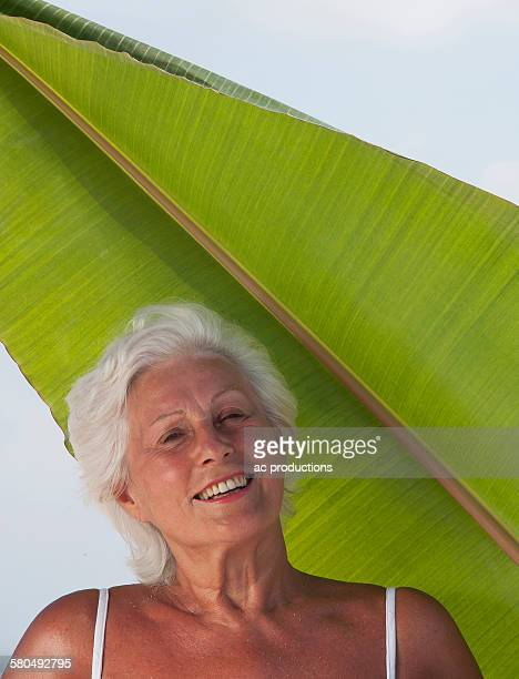 older caucasian woman standing under leaf - vilamendhoo stock photos and pictures