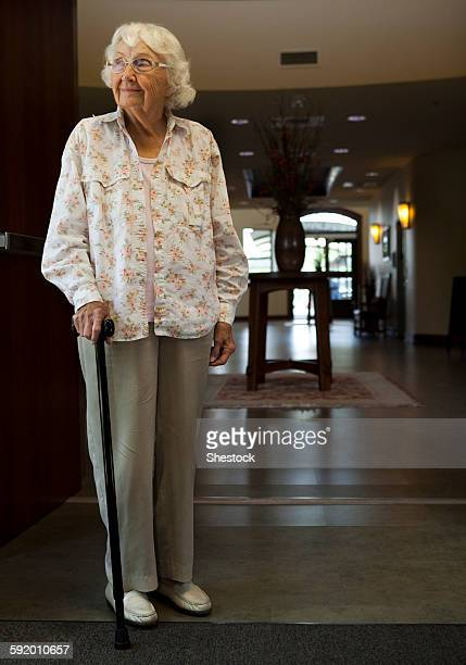 Older Caucasian woman standing with cane in retirement home