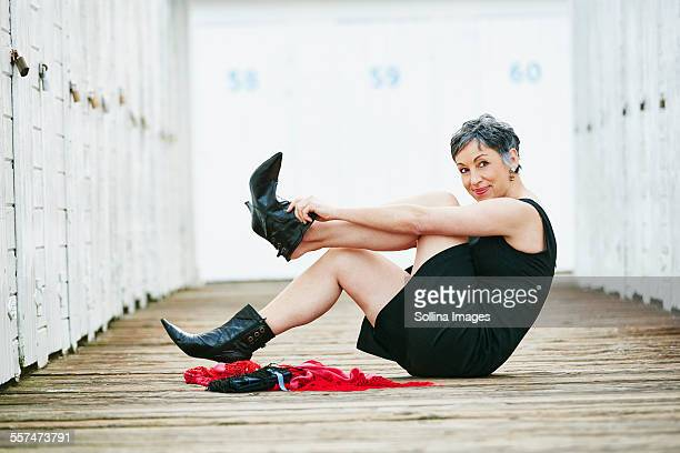 older caucasian woman taking off boots on wooden dock - women trying on shoes stock pictures, royalty-free photos & images