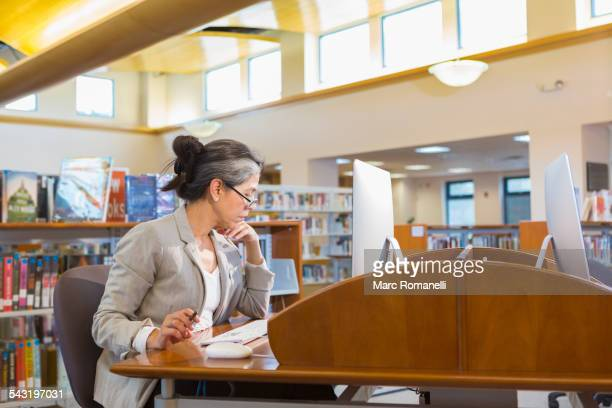 Older Caucasian woman using computer in library