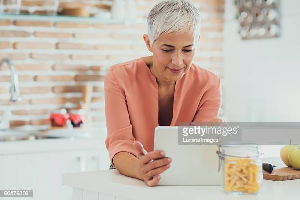 Older Caucasian woman using digital tablet in kitchen