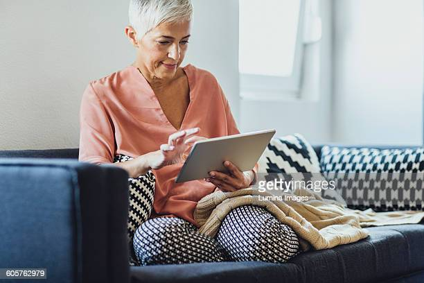 older caucasian woman using digital tablet on sofa - using digital tablet stock pictures, royalty-free photos & images