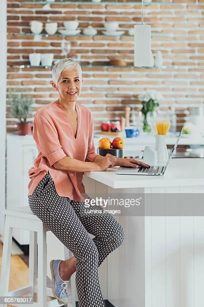 Older Caucasian woman using laptop in kitchen