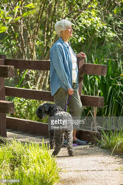 Older Caucasian woman walking dog in park