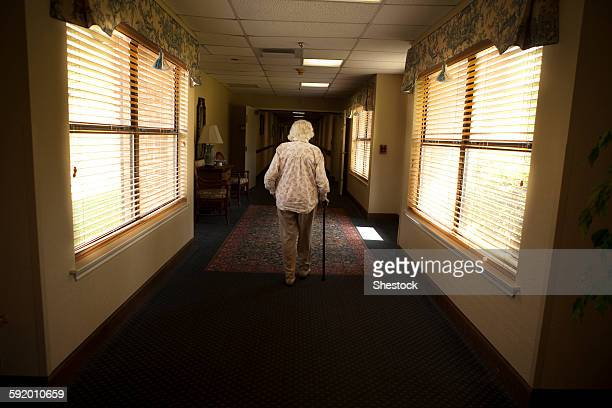 Older Caucasian woman walking with cane in retirement home