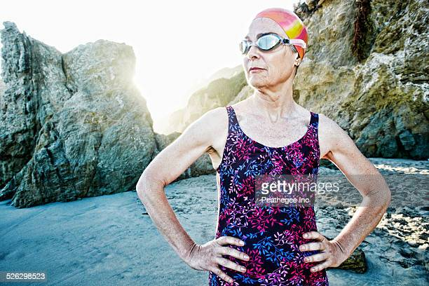 Older Caucasian woman wearing goggles and swimsuit on beach