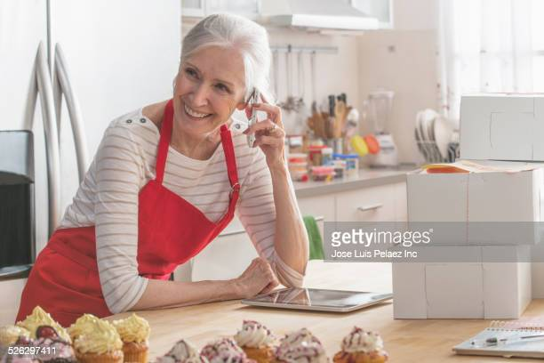 Older Caucasian woman with cupcakes and cell phone