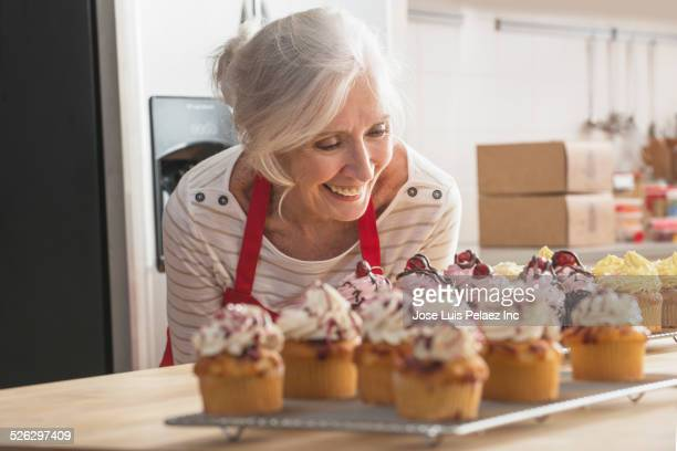 Older Caucasian woman with cupcakes in kitchen