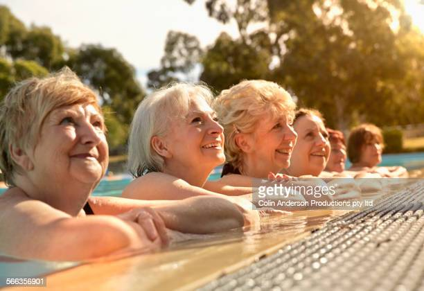 Older Caucasian women leaning on edge of swimming pool