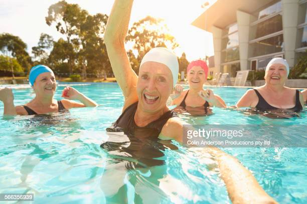 Older Caucasian women playing in swimming pool