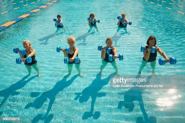 Older Caucasian women taking fitness class in swimming pool