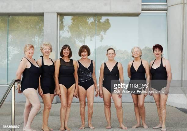 Older Caucasian women wearing black bathing suits at pool