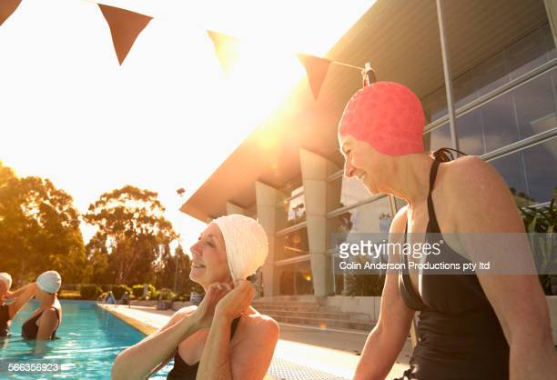 Older Caucasian women wearing swimming caps in pool
