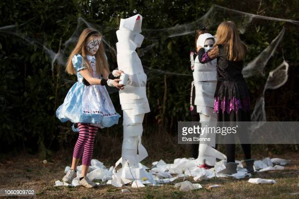 older children playing 'wrap the mummy' halloween game with toilet rolls - wrapped in toilet paper stock pictures, royalty-free photos & images
