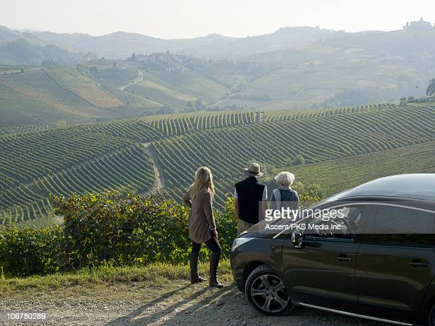 Older couple and daughter look to vineyards, car