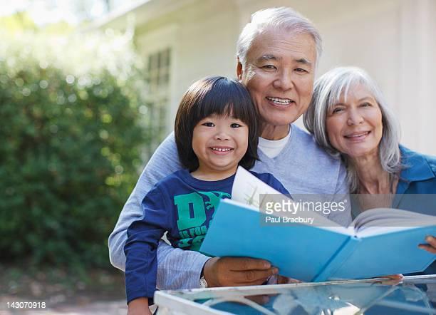 Älteres Paar und Enkel zusammen lesen