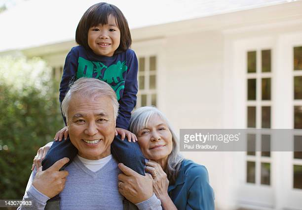 Older couple and grandson standing outdoors