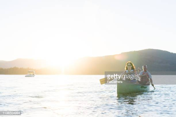 older couple canoe together on a lake at sunset - idaho stock pictures, royalty-free photos & images