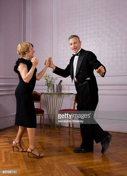 Older couple dancing in ballroom.