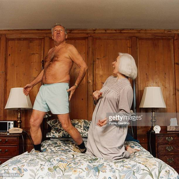 Older Couple Frolicking on Bed