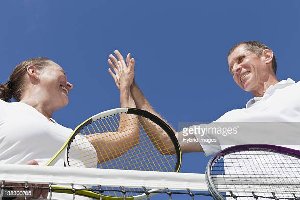 older couple high fiving during tennis - doubles stock photos and pictures