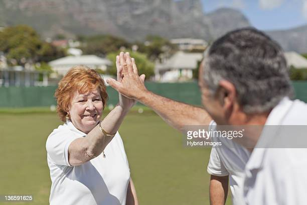 Older couple high fiving outdoors