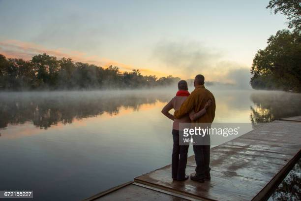 older couple hugging at foggy river at sunrise - sunset lake stock photos and pictures