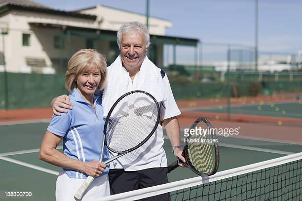 Older couple hugging on tennis court