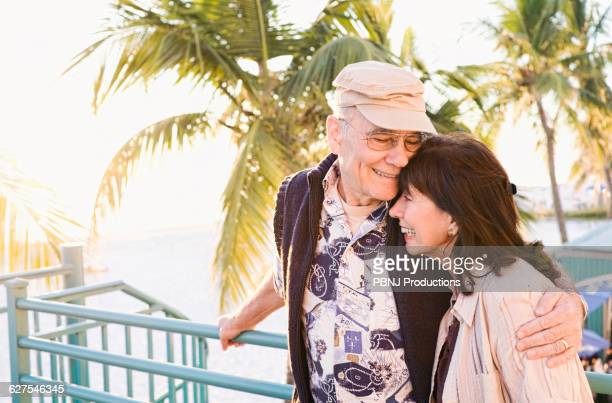 older couple hugging outdoors - fort myers beach stock pictures, royalty-free photos & images