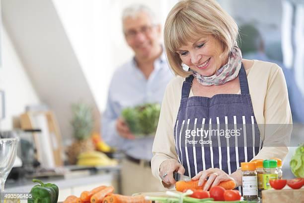 Older couple in kitchen preparing food