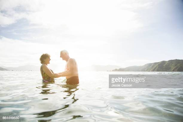 Older couple in sea at sunset