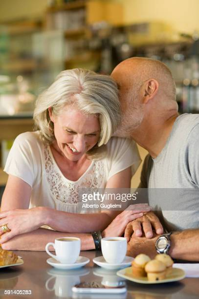 Older couple kissing in cafe