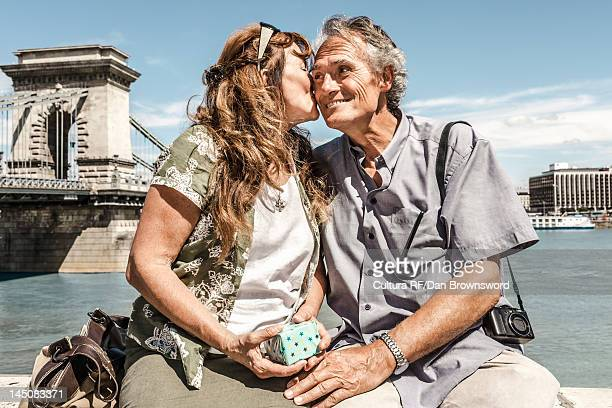 Older couple kissing on bridge