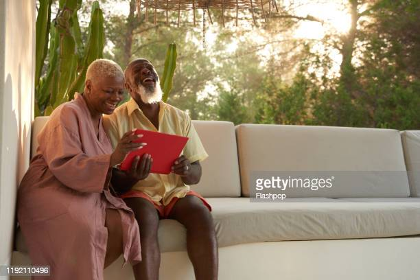 older couple laugh with a digital tablet - bonding stock pictures, royalty-free photos & images
