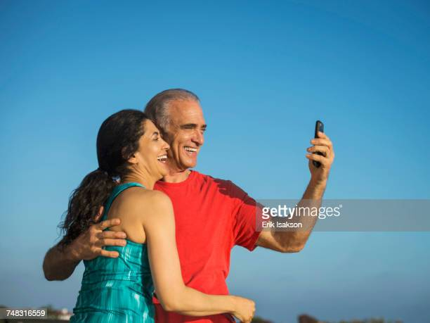 Older couple laughing and posing for cell phone selfie