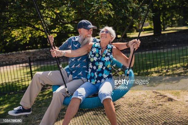 older couple on swing - young at heart stock pictures, royalty-free photos & images