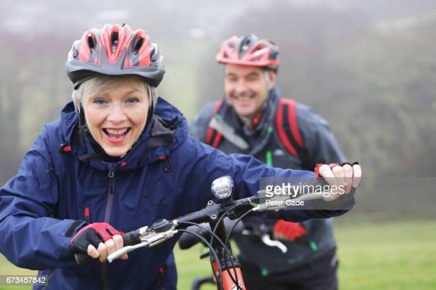 older couple out with bikes on grey day - cycling helmet stock photos and pictures