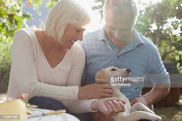 Older couple petting puppy outdoors
